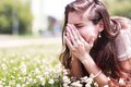 Pollen allergy girl sneezing in a field of flowers Royalty Free Stock Photos