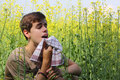 Pollen allergy tennage boy sneezing in a flowers meadow concept seasonal Stock Image