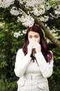 Pollen allergy a woman sneezing because of in a garden in the spring Stock Image