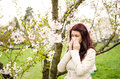 Pollen allergy a woman sneezing because of in a garden in the spring Stock Photo