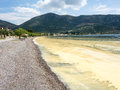 Pollen slick vast floating on shore gulf of corinth greece caused by excessive late spring production naturally occurring Royalty Free Stock Photo