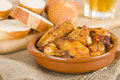 Pollo al ajillo garlic chicken wings traditional spanish tapas dish served with bread and beer Royalty Free Stock Image