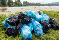 Polluted river banks garbage bags piled up on Royalty Free Stock Photography
