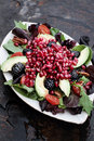 Pomegranate avocado and blackberrry salad a healthy with tomatoes almonds argula lettuce over a rustic background Royalty Free Stock Image