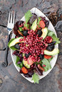 Pomegranate avocado and blackberrry salad a healthy with tomatoes almonds argula lettuce over a rustic background Stock Photography