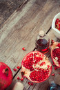 Pomegranate and bottles of essence or tincture top view on wooden rustic table Royalty Free Stock Photography