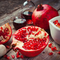 Pomegranate and bottles of essence or tincture on wooden rustic table Royalty Free Stock Photography