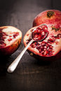Pomegranate fruit on a old wooden table with a silver spoon Royalty Free Stock Image