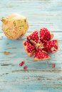 Pomegranate whole and open on wooden table Royalty Free Stock Image