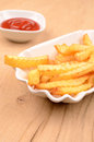 Pommes frites in a white bowl with tomato sauce Stock Photography