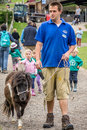 Pony on a walk farmer taking little for to show it to children visiting farm Royalty Free Stock Photo