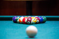 Pool balls on a pool table green felt racked and ready to break the cue ball is visible out of focus in the foreground Stock Photography