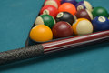 Pool billiard balls and stick on a green felt table Royalty Free Stock Photos