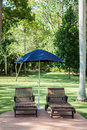 Pool chairs with umbrella in a relaxing setting Royalty Free Stock Image