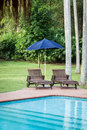 Pool chairs with umbrella in a relaxing setting Stock Images