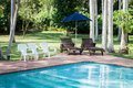Pool chairs with umbrella in a relaxing setting Stock Photography
