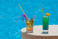 Pool coctails two glasses of with the blue water in background Royalty Free Stock Photo