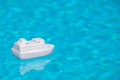 Pool cruise travel background of a toy passenger ship floating in the rippled water of a blue swimming Stock Photo
