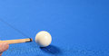 Pool cue and ball person with a about to strike a white on a blue baize table Stock Photos