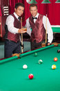 Pool game two cheerful young men playing and drinking Royalty Free Stock Photography