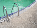 Pool ladder step with swimming pool in the morning. Royalty Free Stock Photo