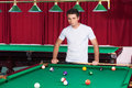 Pool player confident young holding cue and looking at the billiard table Royalty Free Stock Photo