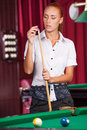 Pool player confident young woman holding cue Stock Photo