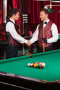 Pool players two cheerful young handshaking and smiling Royalty Free Stock Image