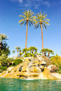 Pool of water with row of palm trees fountain over boulders Stock Image