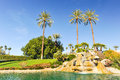 Pool of water with row of palm trees fountain over boulders Royalty Free Stock Photo
