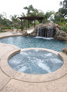 A pool with a waterfall in a luxury backyard Royalty Free Stock Images