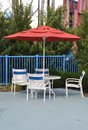 Poolside chairs and table with umbrella Royalty Free Stock Photo