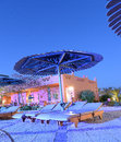 Poolside loungers at dusk under a large parasol outside a modern architect designed hotel Stock Photography