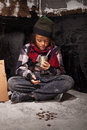 Poor beggar child boy reviews the money he received looking into tin can Royalty Free Stock Images