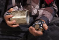 Poor beggar child counting coins closeup on hands dirty holding tin can Royalty Free Stock Photos