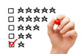 Poor rating hand putting check mark with red marker on one star Royalty Free Stock Images