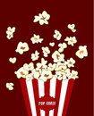 Popcorn exploding inside the red white striped packaging. Vector cinema food. Container with overflowing maize Royalty Free Stock Photo