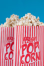 Popcorn get your fresh popcorn bags of on a blue background shallow dof Stock Photos