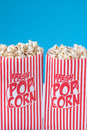 Popcorn get your popcorn on a blue background shallow dof Stock Photography