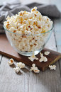 Popcorn in glass bowl over wooden background Stock Photography