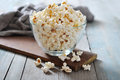 Popcorn in glass bowl over wooden background Royalty Free Stock Image