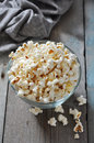 Popcorn in glass bowl over wooden background Stock Image