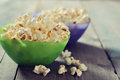 Popcorn in plastic bowls over wooden background Royalty Free Stock Photo