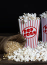Popcorn popped in retro style red striped paper boxes un popped corn in retro burlap bag and in foreground Royalty Free Stock Photos