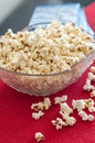Popcorns in a bowl on a table with dvd blu ray and remote controls Stock Image