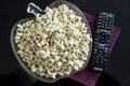 Popcorns in a bowl on a table with dvd blu ray and remote controls Stock Photography
