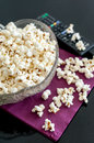 Popcorns in a bowl on a table with dvd blu ray and remote controls Royalty Free Stock Image