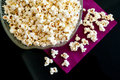 Popcorns in a bowl on a table with dvd blu ray and remote controls Royalty Free Stock Photo