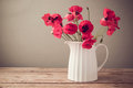 Poppy flower bouquet in white jug on wooden table Royalty Free Stock Photo