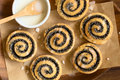 Poppy seed rolls homemade with icing on wooden plate photographed overhead with natural light selective focus focus on the top of Royalty Free Stock Image